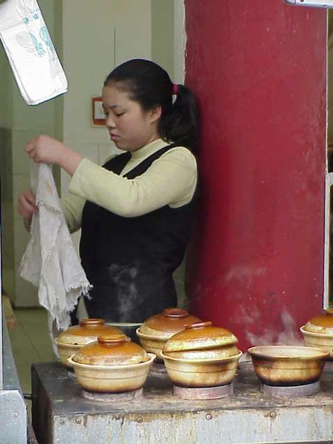 Sidewalk restaurant, girl with pots